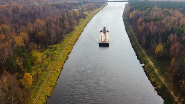 川のタグボートは川の貨物のはしけを動かす。秋の風景 - はしけ点の映像素材/bロール