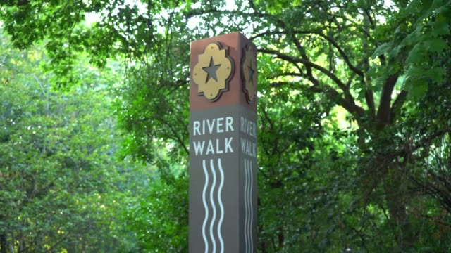 river walk sign with trees in background panning video - san antonio texas stock videos & royalty-free footage