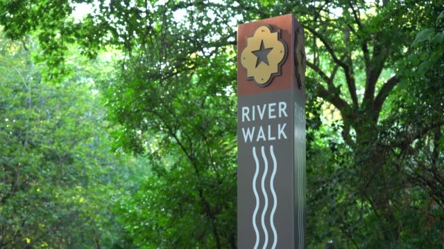 river walk sign with trees in background zooming in - san antonio texas stock videos & royalty-free footage