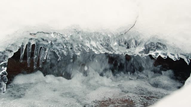 flod vatten rinner under vintern pulver snö närbild - icicle bildbanksvideor och videomaterial från bakom kulisserna