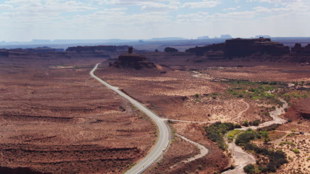 road approaching monument valley - aerial shot - rock formations stock videos & royalty-free footage
