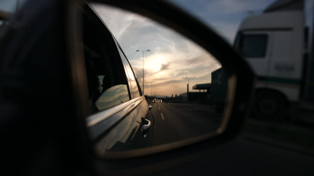 Road at side view mirror during sunset