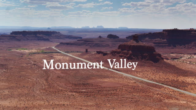 Road Between Buttes in Monument Valley - Drone Shot with Floating Text - video