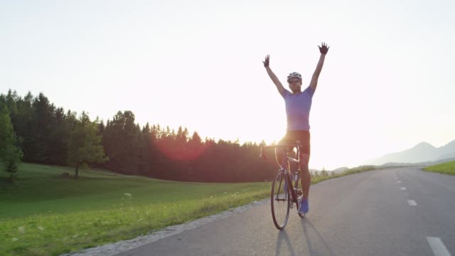 SLOW MOTION: Road biker happy to finish challenging race in golden-lit nature. video