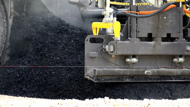 vídeos de stock e filmes b-roll de road construction. asphalt paving machines, close up - bloco