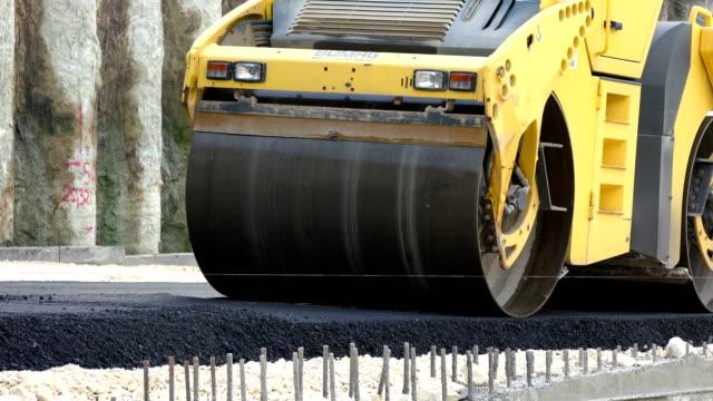 vídeos de stock e filmes b-roll de road construction. compactor roller at asphalting work - alfalto
