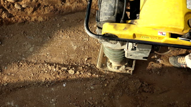 Road construction; worker with a special machine Rams sand video