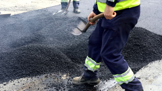 Road Construction Workers Leveling Asphalt