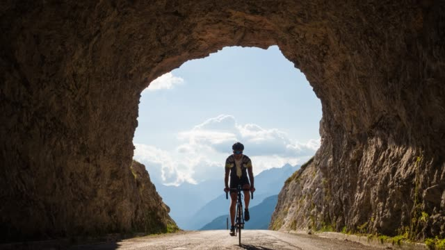 Road cycling into a rocky tunnel Health oriented male athlete riding road bicycle, going into a rocky tunnel on winding mountain road on a beautiful sunny summer day athleticism stock videos & royalty-free footage