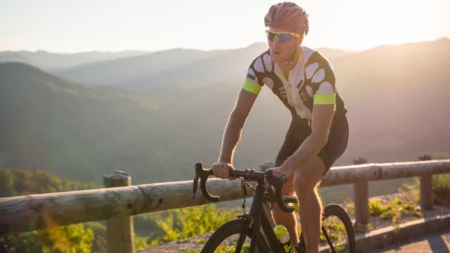 road cycling on a mountain pass - triatleta video stock e b–roll