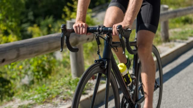 road cycling on a scenic mountain road in nature on sunny day - ciclismo su strada video stock e b–roll