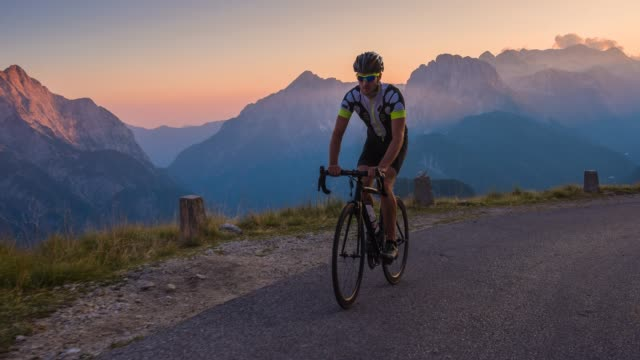 road cycling on a scenic route at sunset, mountains in background - ciclismo su strada video stock e b–roll