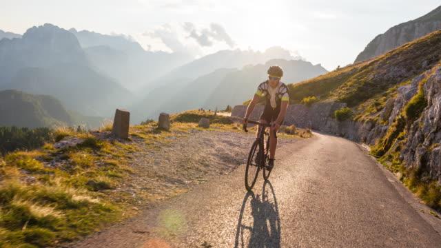 road cycling on winding mountain road - ciclismo su strada video stock e b–roll