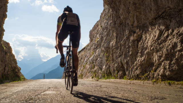 road cycling through a rocky tunnel on mountain road - ciclismo su strada video stock e b–roll