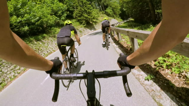 POV Road cycling with Two male cyclists down a mountain road in sunshine