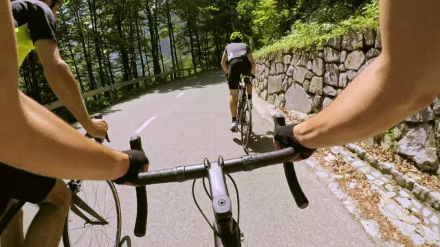 ciclista pov road superato da due ciclisti maschi sulla soleggiata strada di montagna - ciclismo su strada video stock e b–roll