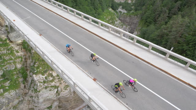 AERIAL Road cyclist crossing a bridge above a gorge