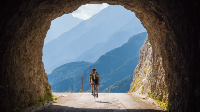 vídeos de stock e filmes b-roll de road cyclist going into a rocky tunnel in mountains - desportista