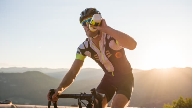 road cyclist hydrating while pushing his limits cycling uphill - evento ciclistico video stock e b–roll