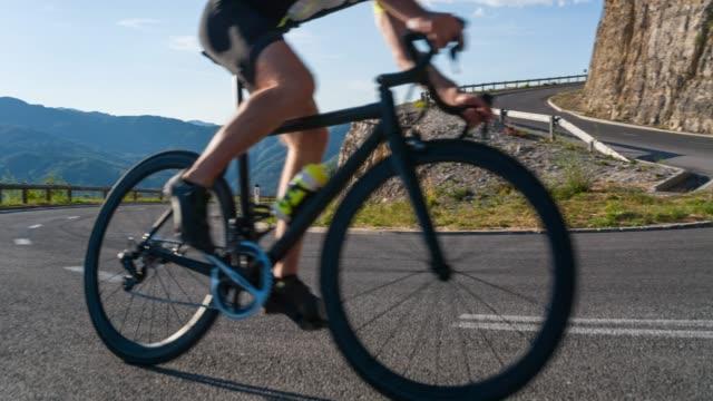 ciclista su strada che svolta su una strada tortuosa - passo montano video stock e b–roll