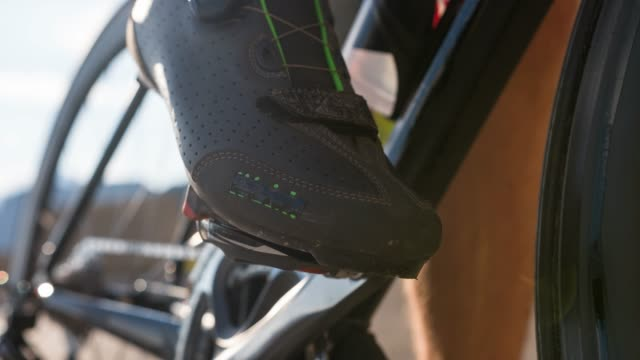 ciclista su strada che sgancia le scarpe da ciclismo dal pedale della bici da strada - ciclismo su strada video stock e b–roll