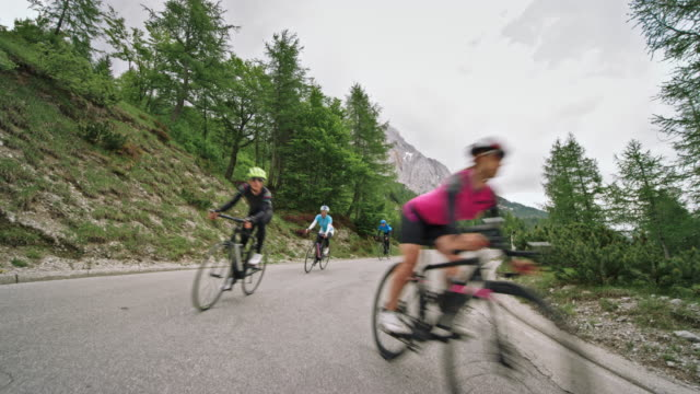road cyclists descending the mountain on an asphalt road on a cloudy day - ciclismo su strada video stock e b–roll