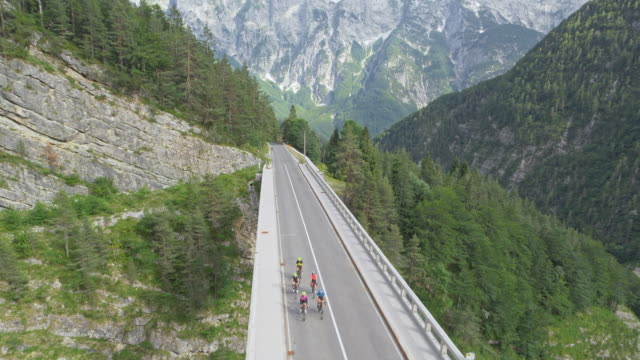 AERIAL Road cyclists riding across a viaduct in the mountains