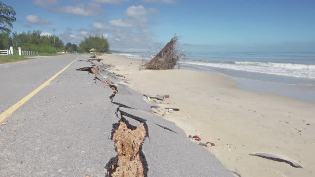Road damaged by erosion 4K DOLLY : Road damaged by erosion. Coastal erosion from sea waves in southern Thailand. earthquake stock videos & royalty-free footage