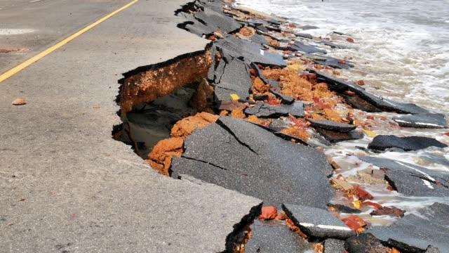 vídeos de stock, filmes e b-roll de estrada destruir a estrada de asfalto de ondas do mar. - erodido