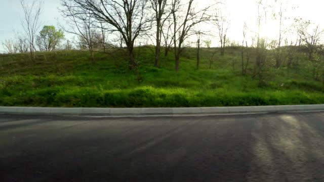 straße fahren pov entlang grüner horizont und sonne - seitenansicht stock-videos und b-roll-filmmaterial