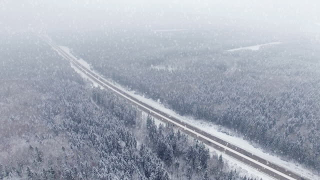 4K. Road in the winter forest with driving cars at snowfall. Aerial panoramic view. Vanishing point perspective video