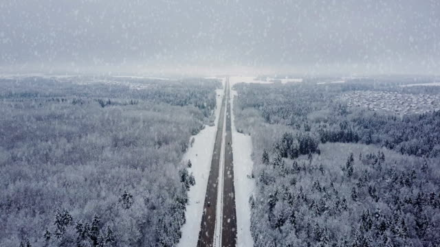 4K. Road in winter forest with driving cars at snowfall video