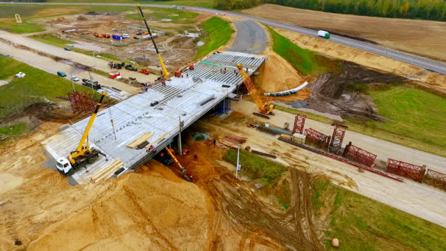 vídeos de stock e filmes b-roll de road junction construction. top view. sky view of bridge repair on highway road - ponte