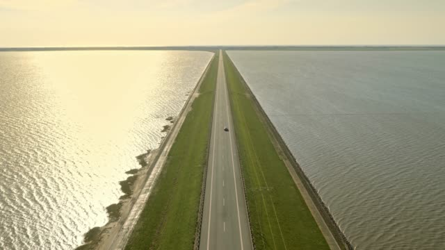 aerial road on a dam in sunshine - grandangolo tecnica fotografica video stock e b–roll