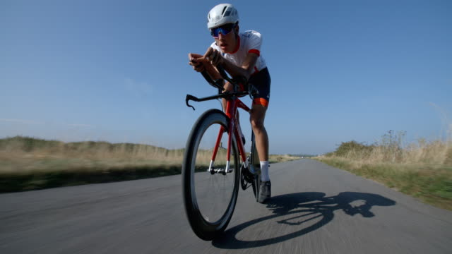 a road race cyclist head down and peddling in slow motion. - ciclismo su strada video stock e b–roll