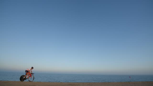 a road racing cyclist ring along the ocean beach road. - ciclismo su strada video stock e b–roll