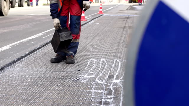 Road repair. Work details, workers pour resin road surface to cover the asphalt.