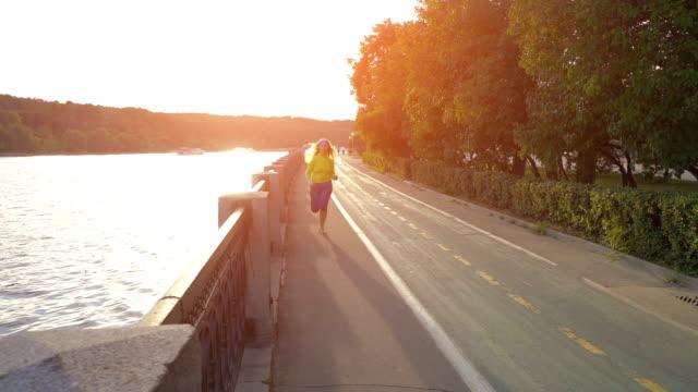 road runner kvinna kör i parken på kvällen - tävlingsdistans bildbanksvideor och videomaterial från bakom kulisserna