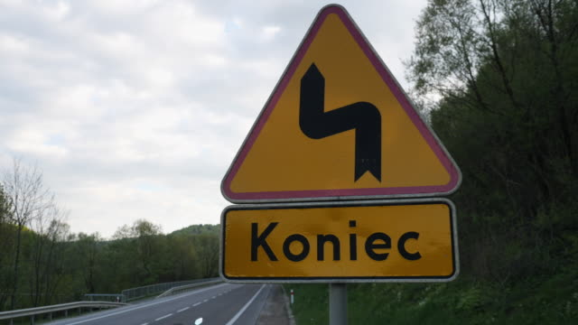 Road sign winding road and the inscription in Polish - the end