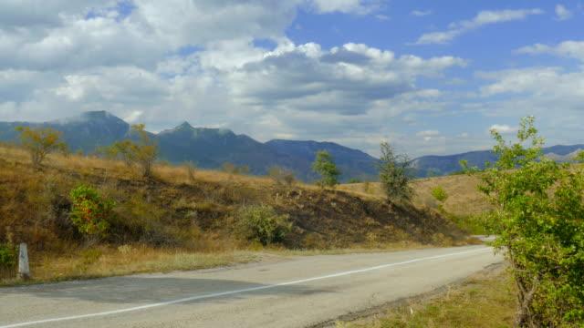 vídeos de stock e filmes b-roll de road through hilly terrain - berma da estrada