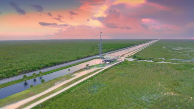 aerial road through the everglades, fl at sunset - болото стоковые видео и кадры b-roll