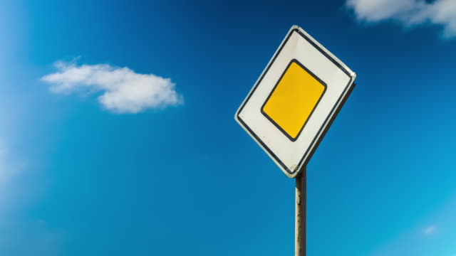 Road traffic control sign. Rules of the road, the main road. Car traffic. Sign against the sky with clouds