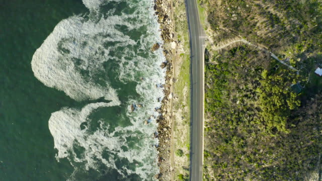 Road trip anyone? 4k video footage of a busy road in between Cape Town's terrain and the ocean which surrounds it western cape province stock videos & royalty-free footage