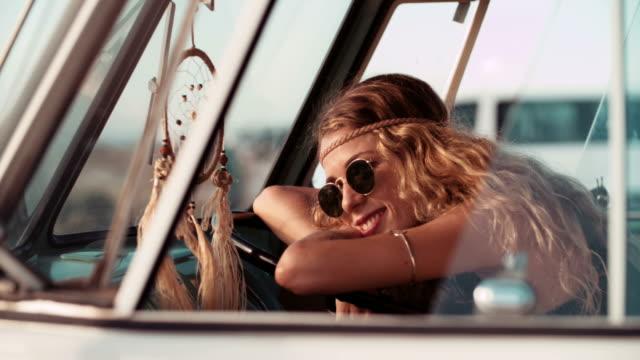 viaggio retrò hipster ragazza seduta in van in spiaggia - hippy video stock e b–roll