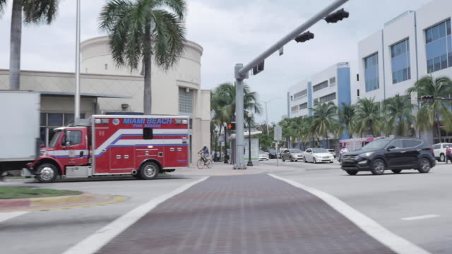 Miami Beach, USA - April 12, 2019: Road trip in Miami Beach. Yellow Cab Taxi, Red sportive car, Ambulance Truck, Palm trees, road crossing, people walking, motorcycle driver, pink bus and white truck. Miami Beach, USA - April 12, 2019: Road trip in Miami Beach. Yellow Cab Taxi, Red sportive car, Ambulance Truck, Palm trees, road crossing, people walking, motorcycle driver, pink bus and white truck. florida us state stock videos & royalty-free footage