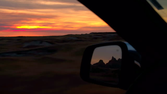 FPV: Road trip through Badlands National Park desert at amazing reddish sunset Road trip through Badlands National Park in the Great Plains at amazing reddish sunset. Driving through vast grasslands at beautiful sunrise, sandstone mountains reflecting in wing mirror of a car country geographic area stock videos & royalty-free footage