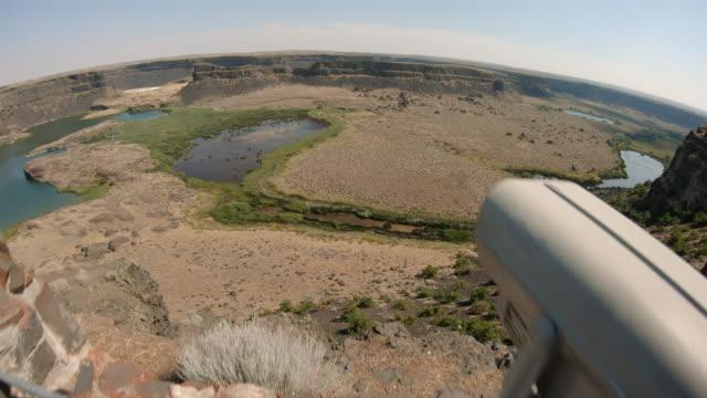 砂漠の渓谷で金属双眼鏡を見渡す少年のロードトリップ観光ビュー ビデオ