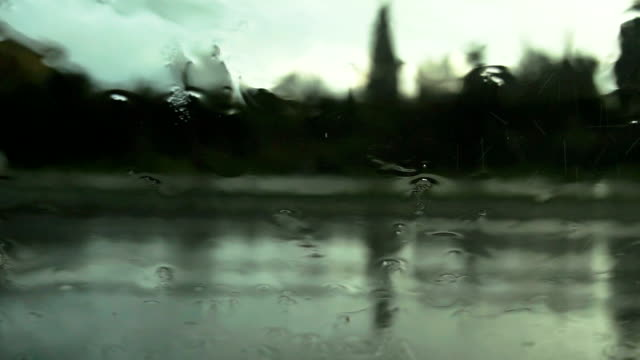Road view through car windshield with rain drops video
