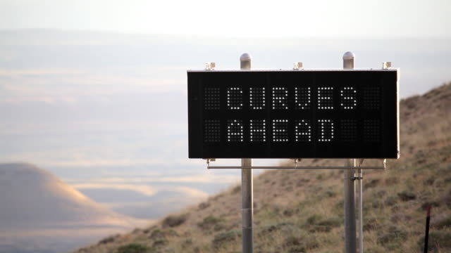 HD road warning sign slow curves ahead video