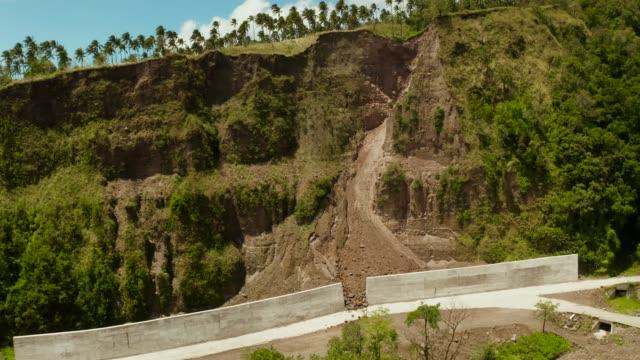 vídeos de stock, filmes e b-roll de estrada com as cercas concretas no console de camiguin, filipinas. proteção da estrada de rockfalls e deslizamentos de terra - erodido